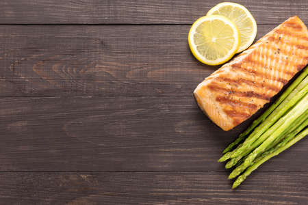 cooked: Grilled salmon with lemon, asparagus on wooden background.