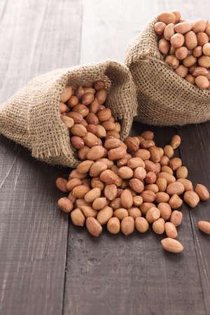 goober peas: Peanut in sacks on the wooden table.