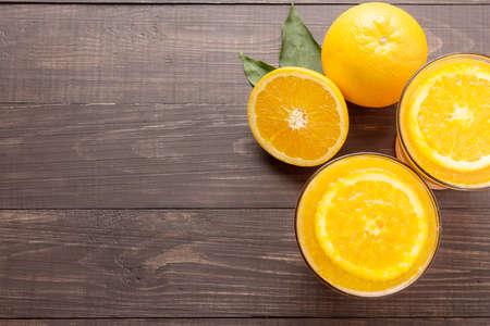 copies: Fresh orange juice and oranges on wooden background.