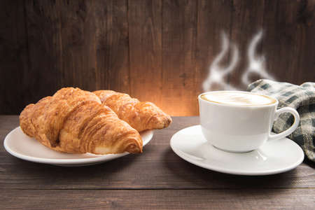 breakfast cup: Breakfast coffee cup and croissant on wooden background.