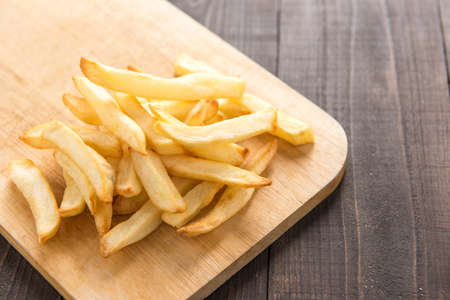 cutting board: French fries on cutting board on wooden table. Stock Photo