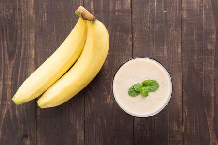 Banana smoothie and fresh banana on wooden table.
