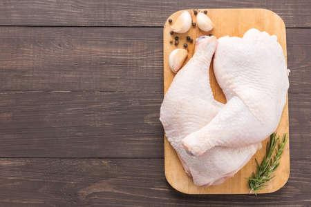 木製の背景にまな板の上の鶏の生脚。