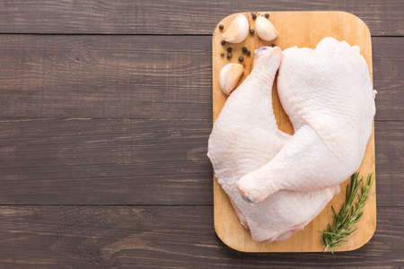 Raw chicken leg on cutting board on wooden background. Stock Photo