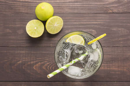 glass table: Fresh cocktail with soda, lime on a wooden background.