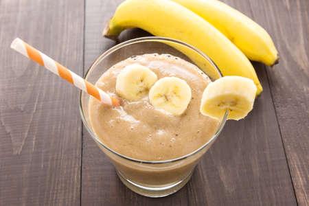 chocolate shake: Banana smoothie and fresh banana on wooden table.