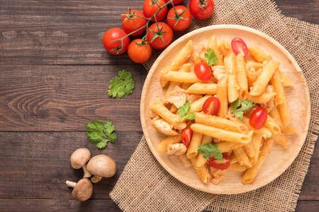 Penne pasta in tomatensaus met kip op een houten achtergrond.