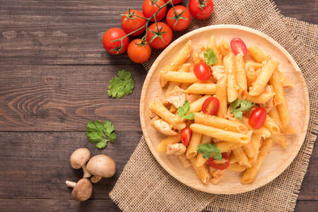 Penne pasta in tomato sauce with chicken on a wooden background.