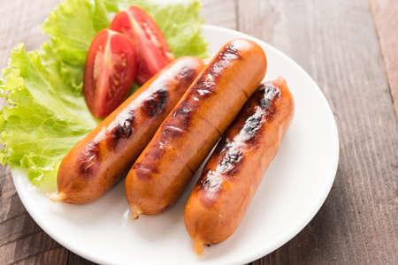 plato de comida: salchichas establecidos en la lechuga con las rodajas de tomate.