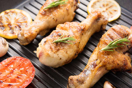 Grilled chicken drumstick and vegetables in a pan.