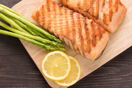 grill: Grilled salmon and lemon, asparagus, on the wooden table.