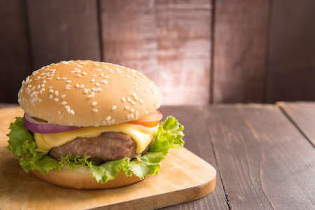 cheeseburgers: Cheeseburgers on buns with succulent beef on the wooden background. Stock Photo