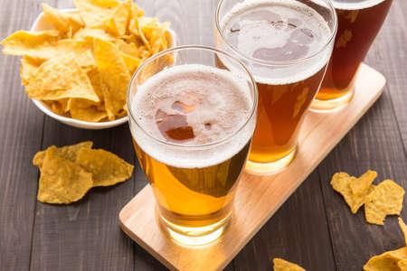 cerveza: Surtido de vasos de cerveza con nachos chips en una mesa de madera.