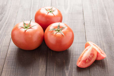 halved  half: Fresh tomato on the brown wooden background. Top view. Stock Photo