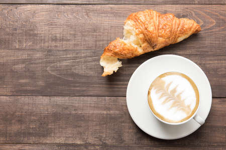 cappuccino: Coffee cup and fresh baked croissants on wooden background. Top View.