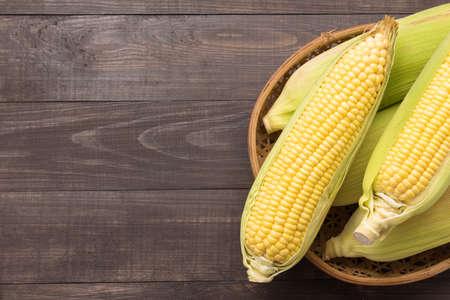 yellow corn: Fresh organic yellow sweet corn on wooden table. Top view.