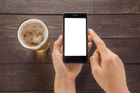 El uso de teléfonos inteligentes al lado de cerveza en el pub. Foto de archivo - 55642619