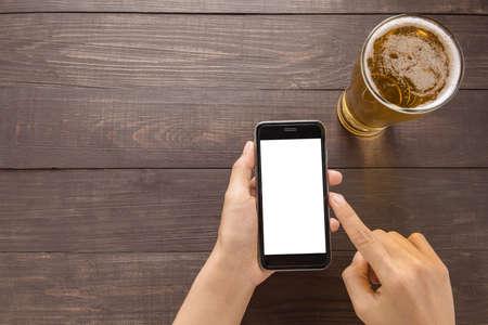 cerveza: El uso de teléfonos inteligentes al lado de cerveza en el pub.