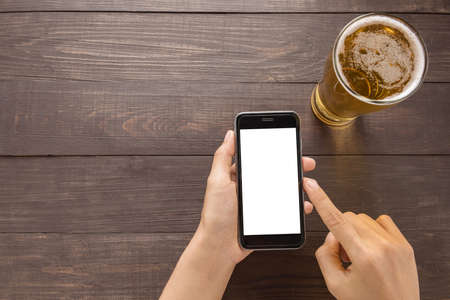 Using smartphone beside of beer in the pub. Standard-Bild