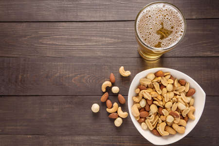 Glass of beer and almond, macadamia, peanut, cashew nut on the wooden background.