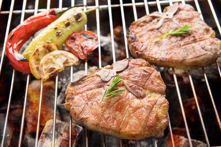 pork: Grilled pork chop and vegetables on the flaming grill. Stock Photo