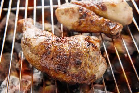 pollo a la brasa: Muslo de pollo a la parrilla sobre las llamas en una barbacoa. Foto de archivo