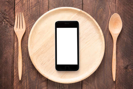 table set: Eating smartphone on set of fork,spoon and dish wood on wooden table.