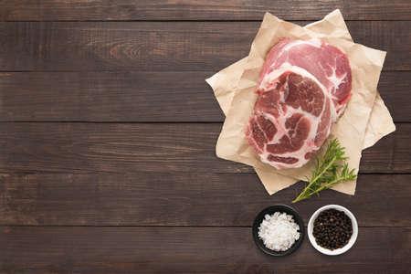 seasoning: Top view raw pork chop steak and garlic, pepper on wooden background.