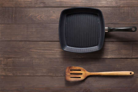turner: Cast iron griddle pan and turner wood on wooden background.