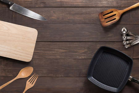 pans: Various kitchenware utensils on the wooden background.