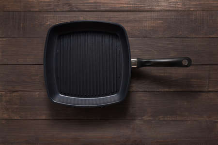 cast iron: Cast iron griddle pan on wooden background.