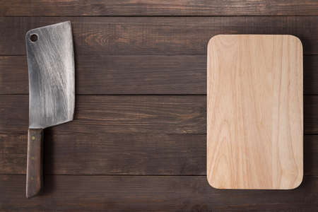 cleaver: Cleaver and cutting board on the wooden background. Stock Photo