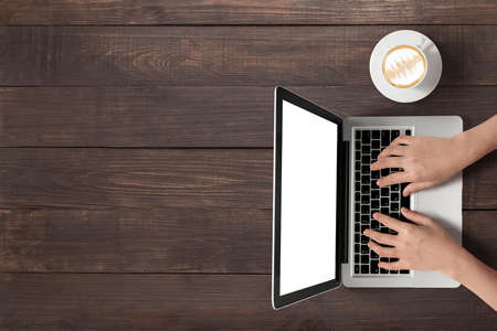 Using laptop and a cup of coffee on wooden background. Foto de archivo