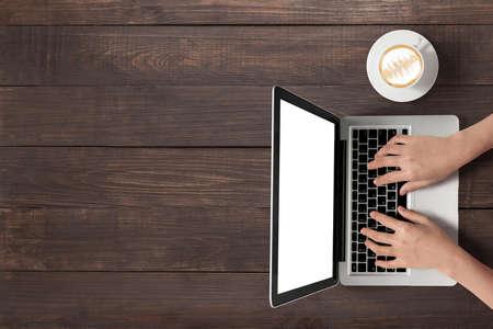 trompo de madera: Usando la computadora portátil y una taza de café sobre fondo de madera.