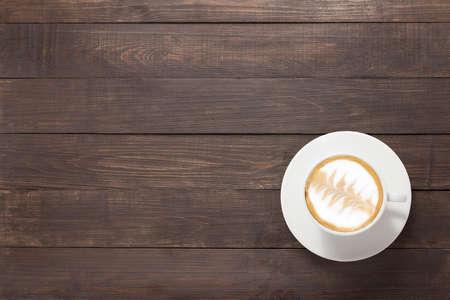 木製の背景のコーヒー カップ。平面図です。
