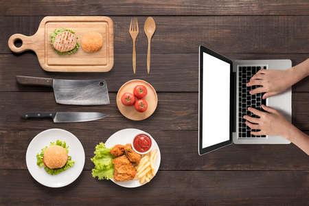 HAMBURGUESA: La búsqueda de convertir la comida rápida (hamburguesas, pollo frito, patatas fritas, tomate) en el fondo de madera.