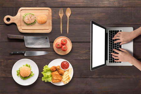 table top: Searching for making fast food (burgers, fried chicken,french fries, tomato) on the wooden background.