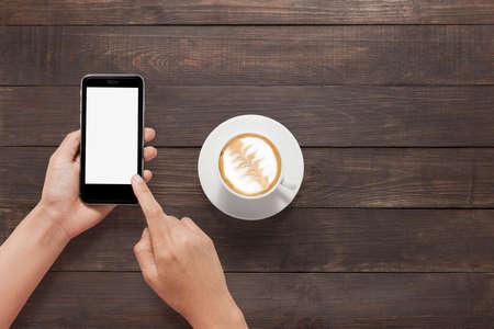 Met behulp van smartphone naast koffie op houten tafel.
