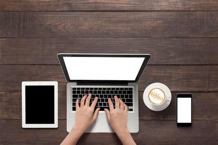 Met behulp van laptop, tablet, smartphone en een kopje koffie op houten achtergrond.