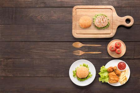 Eten concept Burgers, gebakken kip, patat en tomaat op de houten achtergrond.