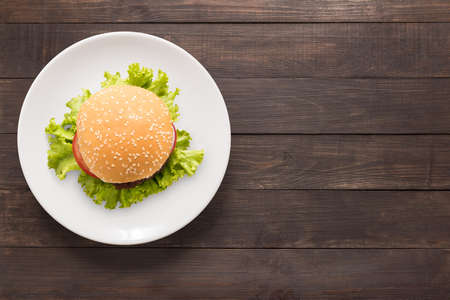 gourmet burger: Top view BBQ burger on white dish on wooden background. Stock Photo
