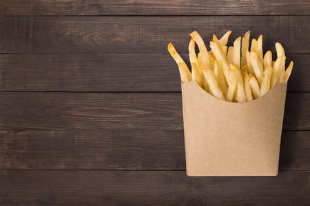 French fries on wooden background.