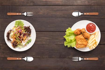 新鮮なサラダとフライド チキンと木製の背景にフライド ポテト。対照的な食品。