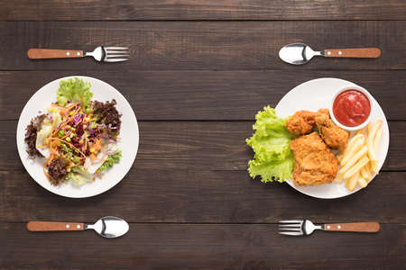 Verse salade en gebakken kip en patat op de houten achtergrond. contrasterende voedsel.
