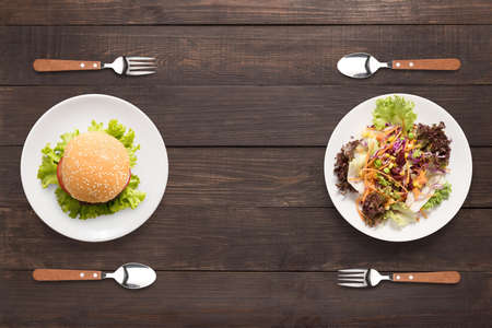 Ensalada y hamburguesa en el fondo de madera. contraste de alimentos. Foto de archivo - 57558390