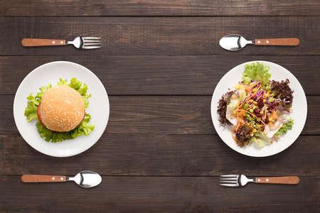 comida chatarra: ensalada y hamburguesa en el fondo de madera. contraste de alimentos. Foto de archivo