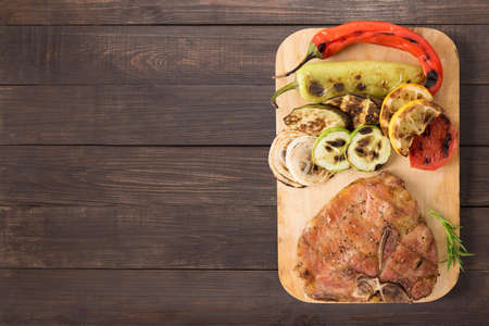 grilled pork chop: Grilled pork chop and vegetables on the wooden background. Copyspace for your text. Stock Photo