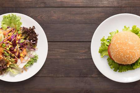 alimentos saludables: ensalada y hamburguesa en el fondo de madera. contraste de alimentos. Foto de archivo