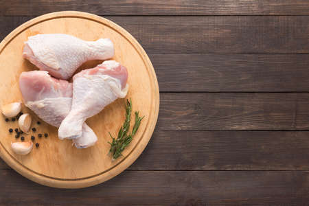 raw: Raw chicken drumsticks on cutting board on wooden background. Copy space for your text.