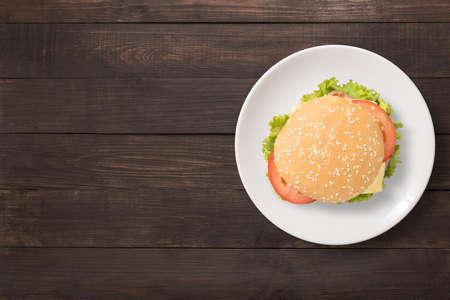 木製の背景の白い皿に平面図バーベキュー ハンバーガーです。テキストのスペースにコピーします。 写真素材